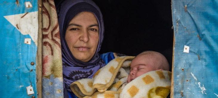 シリアから難民としてレバノンへ逃れ仮住まいのテントで生後2カ月の赤ん坊を抱く母親